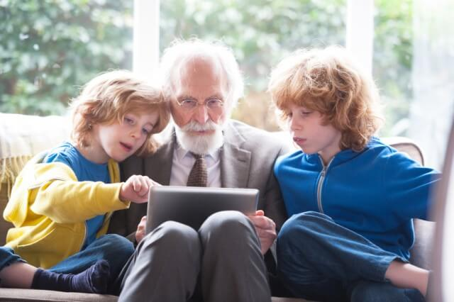 grandfather and grandsons using a digital tablet